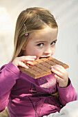 Girl (3-4 years) eating a bar of chocolate, Munich, Germany