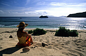 Woman sitting on a sandy beach watching a cruise ship go by, Navadra Island with MV Reef Escape in background, Navadra Island, Mamanuca group, Fiji, South Sea