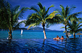 Couple in the pool of the luxury Beach Club Resort on Hamilton Island, Whitsunday Islands, Great Barrier Reef, Australia