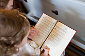 Girl with hymnbook attending divine service during a wedding, Hauneck Oberhaun, Hesse, Germany