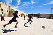 Boys playing football on a market square in Meknes, Marocco, Africa