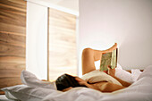 Young woman lying on bed while reading a book, Sand in Taufers, Trentino-Alto Adige/Südtirol, Italy