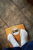 Adult, Adults, Bathroom scales, Color, Colour, Concept, Concepts, Detail, Details, Feet, Floor, Floors, Foot, Human, Indoor, Indoors, Inside, Interior, Measure, Measurement, Measures, Measuring, One, One person, People, Person, Persons, Scales, Single pe