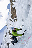 Teenager ice climbing at Corn Diavolezza (man-made icefall), Pontresina, Upper Engadin, Grisons, Switzerland