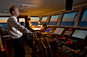 Captain at the helm and helmsman in training on the bridge of a ship, on the Hanse Explorer in the evening, Great Britain