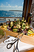Delicious food on board the yacht Hanse Explorer, cold buffet with zucchini, courgette, and vegetables, sea and Scottish coast in the background, Shetland Islands, Scotland, Great Britain