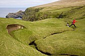 A woman jumping over stream during a hiking tour of Hermaness, Nature Protection Area, island of Unst, Shetland islands, Scotland, Great Britain, UK