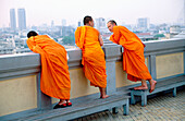 Three monks survey the city at the end of the day from the Golden Mount. Bangkok. Thailand