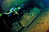 Scuba diver diving in the Umbria shipwreck, Military cars,  Sudan, Africa, Red Sea, Wingate Reef