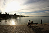 Couple resting on a bench at Lake Constance, Uttwil, Canton of Thurgau, Switzerland