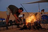 Man lighting camp fire, Offroad 4x4 Sahara Desert Tour, Bebel Tembain area, Sahara, Tunisia, Africa, mr