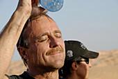 Mann giesst Wasser über sein Kopf, Abkühlung, Offroad Sahara Reisen, Wüsten Tour, Bebel Tembain, Sahara, Tunesien, Afrika, mr