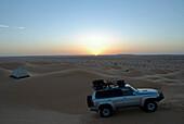 A 4x4 vehicle driving through sand dunes in the desert, 4x4 Sahara Desert Tour, Bebel Tembain area, Sahara, Tunisia, Africa, mr