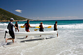 Five people carrying a boat into the water, Sandy Bay Beach, Cape Town, South Africa, Africa, mr