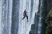 Woman hanging on a rope in front of a waterfall, Grabouw Forest Park, South Africa