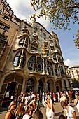 Barcelona,Passeig de Gracia,Casa Batllo by Antonio Gaudi,visitors qeeing in front