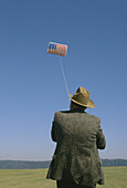 Adult, Adults, America, Amusement, Back view, Caucasian, Caucasians, Chill out, Chilling out, Color, Colour, Contemporary, Exterior, Flag, Flags, Flight, Flights, Fly, Flying, Fun, Hat, Hats, Headgear, Hobbies, Hobby, Horizon, Horizons, Human, Kite, Kite