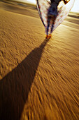 Blurred, Color, Colour, Concept, Concepts, Contemporary, Daytime, Desert, Deserts, Exterior, Female, Heat, Human, Motion, Movement, Moving, One, One person, Outdoor, Outdoors, Outside, People, Person, Persons, Sand, Shadow, Shadows, Single person, Stand,