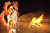 Bonfire and Kiowa Indian in fancy war dress. Indian ceremonial. Gallup. New Mexico. USA