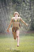 Girl running through lawn sprinkler on summer s day.