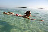 Woman floating in the Dead Sea, Ein Bokek, Israel