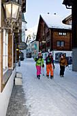 Three skiers walking along snow covered street, Andermatt, Canton Uri, Switzerland