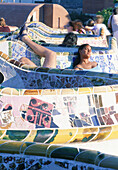 Spain, Catalunya, Barcelona, Young people having a rest at Parc Guell, designed by Antoni Gaudi