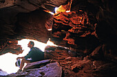 Ranger having a rest in the shadow of a cave. Stock station near Alice Springs. Northern Territory. Australia.