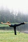 Woman performing yoga along Wark Lake. Ketchikan, Alaska. USA
