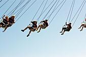 Kids on carnival swing.