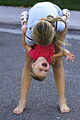 Girl holding laughing toddler upside down