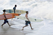 Surfers racing into the water