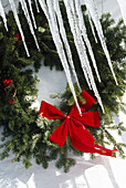 Icicles hanging in front of a Christmas wreath against a white background