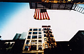 America, American flag, Building, Buildings, Cities, City, Color, Colour, Daytime, Exterior, Fire escape, Flag, Flags, Horizontal, Low angle view, Nobody, North America, Outdoor, Outdoors, Outside, Patriotic, Patriotism, Stairs, Stars and Stripes, U S Fl