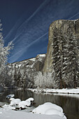 The rock face of El Capitan and the Merced River after a winter snow storm, (aircraft vapour trails in the sky), Yosemite Valley, Yosemite NationalPark, California, USA.