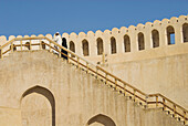 Omani couple climbing the steps to admire the views from the Fort at Nizwa, Oman