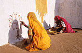 Woman decorating the exterior of their dwelling. Rajasthan. India