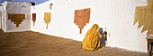 Woman painting the exterior of her dwelling in a village near Jaisalmer. Rajasthan. India