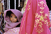 Young child is being held by women in Jodhpur bazaar. Rajasthan. India.