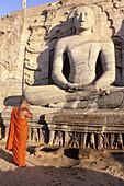 Monk praying in front of Buddha statue, Gal Vihara. Polonnaruva, Sri Lanka