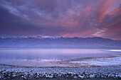 Storm clouds at sunrise over rmountains and desert flood water in salt basin near Badwater, Death Valley, California