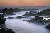 Ocean waves crashing on tidepool rocks at sunset, Bean Hollow State Beach, San Mateo Coast, California