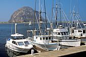 Commercial fishing boats docked at waterfront at Morro Bay, near Morro Rock, San Luis Obispo County coat, California