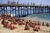 Young boys sitting on sand beach in summer class Junior Lifeguard Camp, Balboa Island, Newport Beach, California