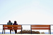 Adult, Adults, Alone, Back view, Bench, Benches, Calm, Calmness, Coast, Coastal, Color, Colour, Contemporary, Couple, Couples, Daytime, Exterior, Female, Full-body, Full-length, Horizon, Horizons, Human, Leisure, Look, Looking, Male, Man, Mature Adult, M