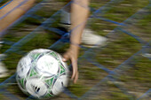 Ability, Action, Activity, Anonymous, Ball, Balls, Blurred, Color, Colour, Contemporary, Country, Countryside, Daytime, Detail, Details, Exterior, Football, Horizontal, Human, Leg, Legs, Leisure, Motion, Movement, Moving, One, One person, Outdoor, Outdoo