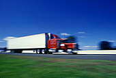 Blurred, Color, Colour, Daytime, Economy, Exterior, Fast, Freight transportation, Highway, Highways, Industrial, Industry, Lorries, Lorry, Motion, Movement, Moving, Outdoor, Outdoors, Outside, Road, Roads, Shipping, Speed, Thoroughfare, Thoroughfares, Tr