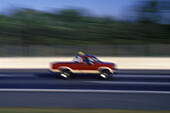 Auto, Automobile, Automobiles, Autos, Blurred, Car, Cars, Color, Colour, Daytime, Exterior, Fast, Highway, Highways, Motion, Movement, Moving, Outdoor, Outdoors, Outside, Pick-up truck, Pickup truck, Red, Road, Roads, Speed, Thoroughfare, Thoroughfares,