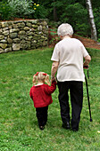 Senior woman, grandmother, walking with cane across backyard lawn with her 3 year old granddaughter.