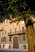 apartment building with arched doorway, balconies and shutters in Verona, Italy